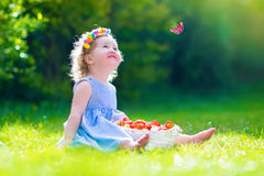 Little girl eating strawberry watching a butterfly Stock Photography