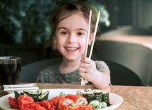 Little girl is eating sushi stock photos