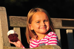 Little girl eating sweet cupcake royalty free stock photography