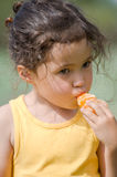 Little girl eating tangerine. A little brunette girl is eating tangerine royalty free stock images