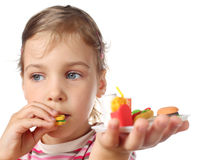 Little girl eating toy miniature burger royalty free stock images