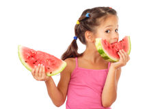 Little girl eating two slices of watermelon Royalty Free Stock Image