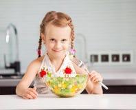 Little girl eating vegetable salad stock images
