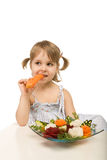 Little girl eating vegetables - chomping a carrot Stock Photo
