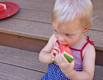 Little Girl Eating Watermelon. This cute little girl is eating a slice of watermelon wearing a 4th of July themed dress Stock Photography