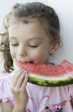 Little girl eating watermelon. With a positive expression Royalty Free Stock Image