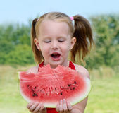 Little girl eating watermelon Stock Photos