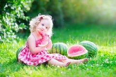 Little girl eating watermelon stock photos