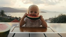 Little girl eating watermelon on outdoor terrace on background evening sunset. Funny girl eating watermelon during evening dinner on summer holiday stock footage