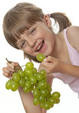 Little girl eating a wine grapes Royalty Free Stock Photography