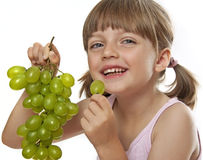 Little girl eating a wine grapes. Isolated on white stock photography