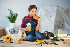 Little girl eating in workshop Royalty Free Stock Photo