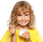Little girl eating yogurt Stock Photos
