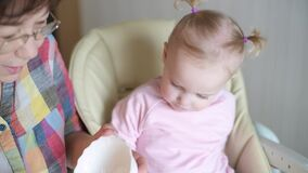 Little girl eating yogurt from a spoon. Grandmother feeds her granddaughter