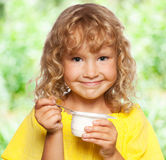 Little girl eating yogurt at summer Royalty Free Stock Photography