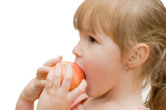The little girl eats an apple Stock Photos