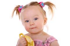 Little girl eats banana Stock Photo