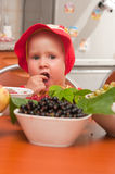 The little girl eats a berry Stock Photo