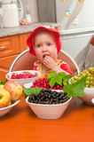 The little girl eats a berry Stock Photos