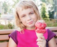 Little girl eats big ice-cream Stock Photo