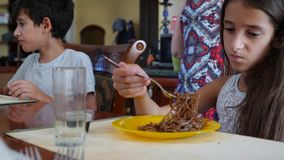 The little girl eats buckwheat noodles with a fork reluctantly. The child refuses to eat. Slow-motion shooting. stock video