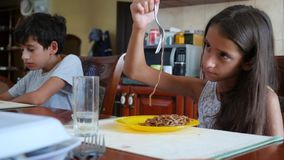 The little girl eats buckwheat noodles with a fork reluctantly. The child refuses to eat. Slow-motion shooting. stock video footage