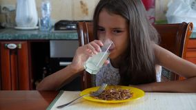 The little girl eats buckwheat noodles with a fork reluctantly. The child refuses to eat. 4 . Slow-motion shooting. stock footage