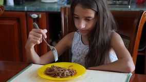 The little girl eats buckwheat noodles with a fork reluctantly. The child refuses to eat. 4 . Slow-motion shooting. stock video footage