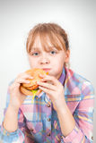 Little girl eats burger above white wall Stock Images