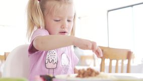 The little girl eats in the cafe. stock footage