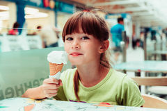 Little girl. Eats in a cafe ice cream Royalty Free Stock Image