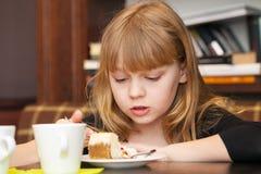 Little girl eats cake with tea Stock Photo