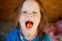 Little girl eats a carrot stock image