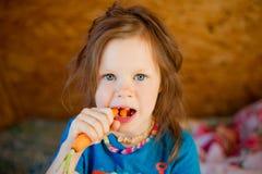 Little girl eats a carrot stock photo