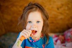 Little girl eats a carrot stock images