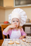 Little girl eats cookies on kitchen Royalty Free Stock Images