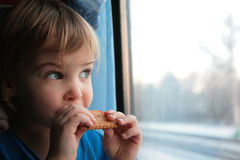 Little girl eats cookies and looks in window Royalty Free Stock Photos