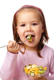 Little girl eats fruit salad Royalty Free Stock Photos