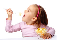 Little girl eats fruit salad Stock Photos