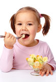 Little girl eats fruit salad royalty free stock photography