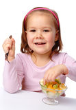 Little girl eats fruit salad Royalty Free Stock Photo