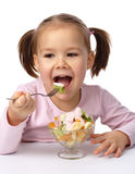 Little girl eats fruit salad Royalty Free Stock Image