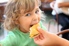 Little girl eats hamburger from mothers's hand stock images