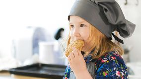 Little girl eats homemade cookies with jam prepared with their own hands royalty free stock photos
