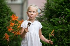 Little girl eats ice cream. European appearance girl in a white dress. Summer day stock image