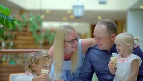 The little girl eats ice cream a horn in big shopping center. Family eats ice cream in the mall. Happy family. Happy stock video footage