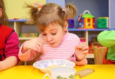 Little girl eats in kindergarten Royalty Free Stock Photography