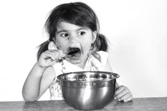 Little girl eats lots of chocolate cream Royalty Free Stock Photography