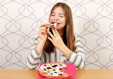 Little girl eats a pie with cherries Royalty Free Stock Photo