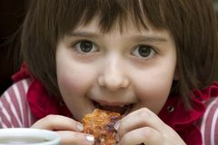 A little girl eats pizza. A little girl 6 yars old smiles and eats pizza Royalty Free Stock Photos